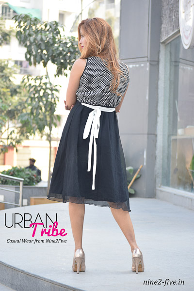 Black & White Checkered Net Yoke With Black Georgette Knee Length Dress. Sleeveless. Pleated Round Neck. It can be machine washed in cold water. Model of 5 feet 4 inches is wearing S Size